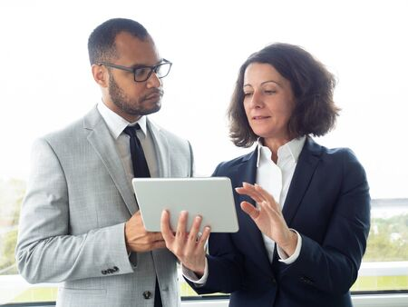 Focused business colleagues using digital tablet. Multiethnic businessman and businesswoman standing and working with tablet pc in office. Business and technology concept