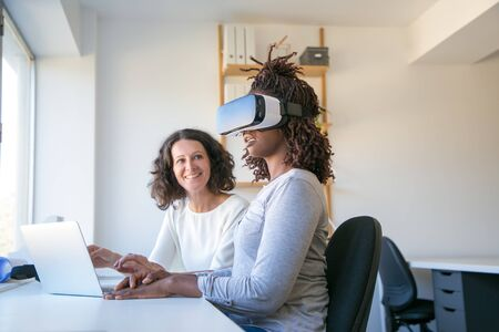 Excited young woman in VR headset watching virtual presentation. Her female colleague looking at her and smiling. Virtual reality experience concept