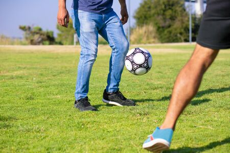 People playing soccer in park. Legs of man in casual jeans kicking football ball on grass. Outdoor activity concept 写真素材
