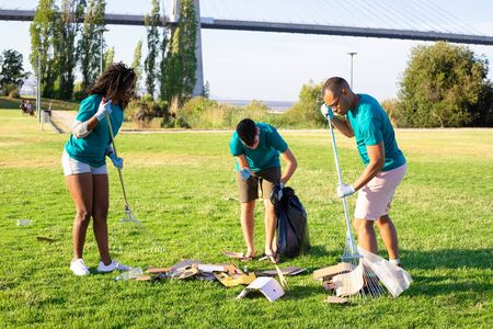 Group of eco volunteers cleaning park lawns. Young men and woman gathering litter with rakes, picking up glass bottles. Trash removal concept 写真素材