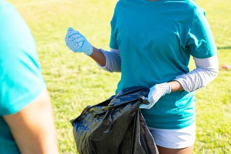 Eco volunteer collecting trash outside. Young woman wearing uniform and protective gloves, holding plastic bags. Voluntary concept