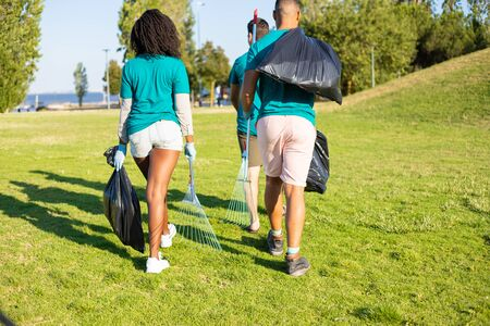 Eco activist team carrying rubbish from city park. Young men and woman walking on grass, holding rakes, plastic bags. Waste collection concept 写真素材