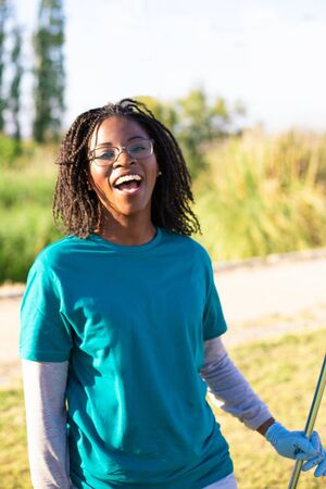 Cheerful excited eco volunteer enjoying cleaning park. Young African American woman wearing uniform and gloves, holding rake, looking at camera, laughing. Happy volunteer concept