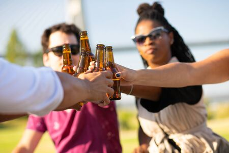 Multiethnic team of friends celebrating outdoors. Hands of young men and women holding bottles, toasting, drinking beer. Party concept