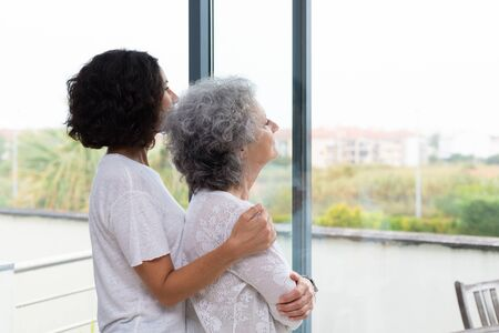 Peaceful middle aged and senior women watching scene from window. Adult daughter embracing old mother at home. Family relationship concept