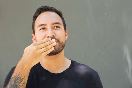Cheerful excited guy keeping secret. Closeup of smiling man covering mouth with tattooed hand and looking away. Secret concept