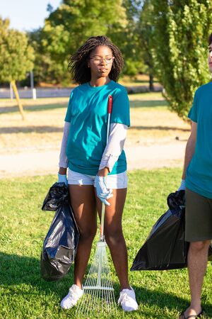 Female eco volunteer ready to start cleaning park. Young African American woman wearing uniform, standing on grass, holding rake and plastic bag. Trash removal concept 写真素材 - 131243845