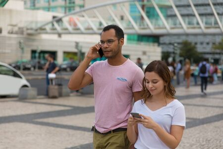 Front view of two people walking on street with smartphones. Handsome African American man talking on phone while walking on street with friend. Communication and technology concept