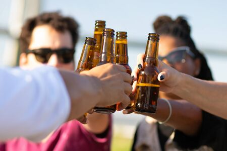 Diverse team of friends drinking beer outdoors. Hands of young men and women holding bottles and toasting. Celebration concept