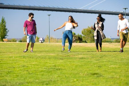 Multiethnic team of friends playing football in park. Young men and women kicking ball on grass. Weekend outdoors concept 写真素材 - 131244993