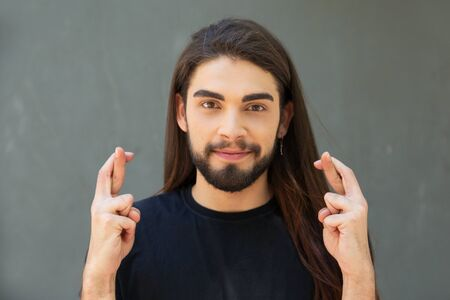 Happy long haired guy making wish. Handsome bearded young man standing over grey background, showing crossed fingers, looking at camera, smiling. Luck concept