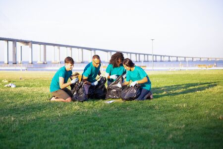 Volunteer group sorting waste and cleaning city lawn. Men and women sitting on grass, picking up litter into plastic bags. Garbage collection concept 写真素材
