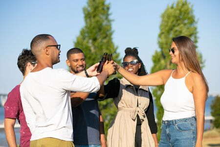 Happy multiethnic friends enjoying beer party in park. Young men and women standing in circle on grass, clinking bottles, smiling, laughing. Old friends meeting concept