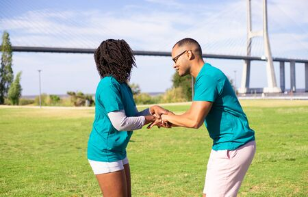 Excited volunteer couple making gesture of unity and teamwork. Man and woman standing on grass, putting their hands together, forming stack of hands. United team concept 写真素材