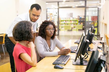 Instructor and trainees discussing corporate software in computer class. Man and women sitting and standing at table, using desktop, pointing at monitor and talking. Corporate training concept Stock Photo