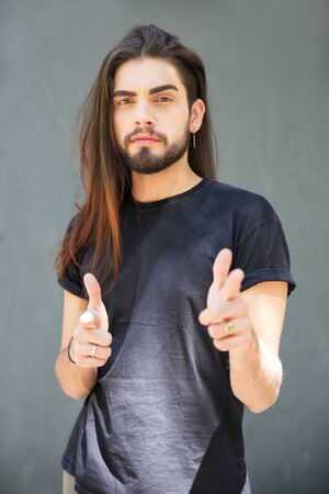 Confident long haired guy making gun shot gesture. Handsome bearded young man standing over grey background, pointing index fingers at camera. Front view. Gesturing concept 写真素材 - 131244286
