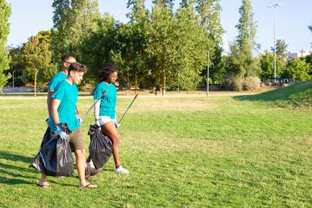 Team of eco activists leaving park after cleaning lawns. Young men and woman walking on grass, carrying rakes, plastic bags and talking. Garbage collection concept