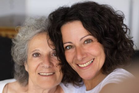 Cheerful senior mother and adult daughter taking selfie. Closeup of happy middle aged woman and elderly lady smiling at camera Family self portrait concept 写真素材