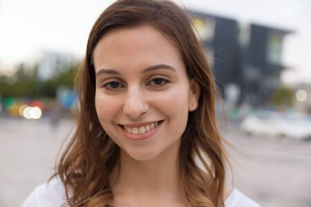 Closeup shot of beautiful young woman with toothy smile. Cheerful Caucasian woman wearing white t-shirt looking at camera. Female beauty concept