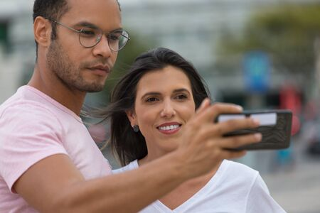 Happy multiracial couple taking self portrait with phone. handsome African American man holding smartphone in outstretched arm. Concept of self portrait