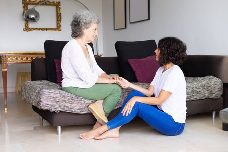 Senior mother and adult daughter discussing problems. Elderly lady and middle aged woman talking in bedroom, holding hands, giving support. Family issues concept