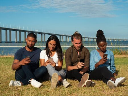 Focused young men and women sitting in line on grass and using smart phones. Diverse team of friends obsessed with gadgets. Social media addiction concept Stock Photo
