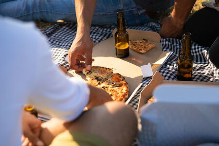 Hand of man taking slice of pizza from box. People gathering around plaid with food and drink, sitting on grass, drinking beer. Eating outdoors concept