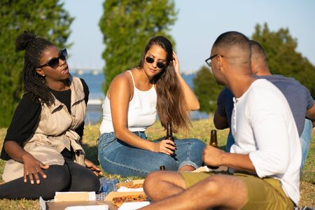 Multiethnic team of friends eating pizza outdoors. Young men and women gathering around plaid with food and drink, sitting on grass, drinking beer, talking. Weekend with friends concept 写真素材