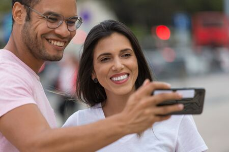 Happy multiracial friends taking self portrait with smartphone. Cheerful couple posing for selfie on street. Concept of self portrait 写真素材