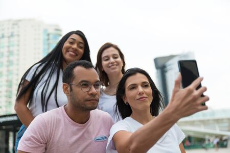 Group of friends taking selfie with smartphone on street. Cheerful young people posing for self portrait. Concept of self portrait 写真素材