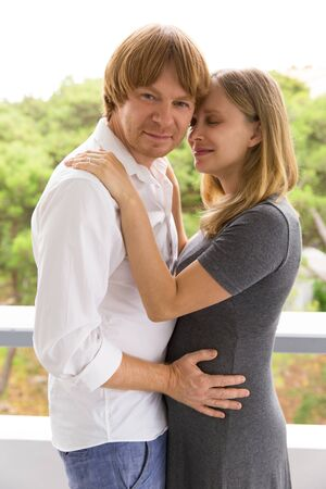 Happy expectant couple posing outside. Man and pregnant woman standing outside, hugging each other, looking at camera. Family and romance concept