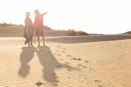 Back view of young couple standing on sandy beach. Husband and wife talking and pointing on seashore during vacation. Vacation concept
