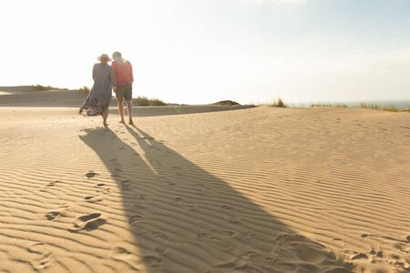Husband and wife strolling on seashore during vacation. Back view of young couple strolling on sandy beach. Vacation concept