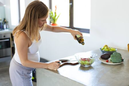 Serious focused expectant mother cooking in kitchen. Pregnant woman standing at table with vegetables, dressing salad with oil. Pregnancy and nutrition concept