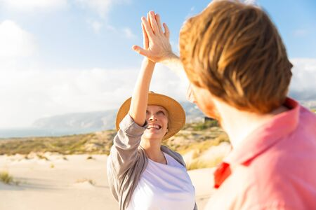 Smiling young couple giving high five on seashore. Happy spouse during summer holiday. Relationship concept