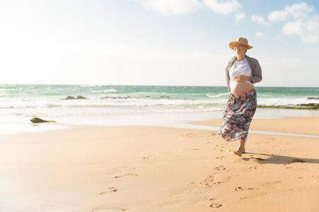 Cheerful future mother walking on beach during vacation. Happy pregnant woman holding hand on belly. Pregnancy concept