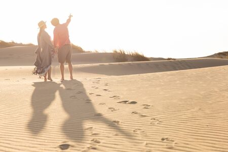 Rear view of young couple standing on sandy beach. Husband and wife looking up on seashore during vacation. Vacation concept Stok Fotoğraf