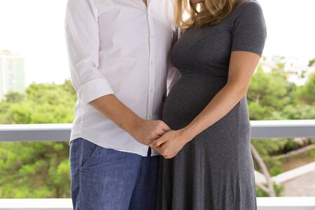 Pregnant couple standing on terrace. Expectant parents hugging and holding hands. Love and family concept