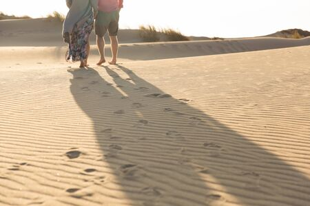Cropped shot of young couple strolling on sandy beach. Legs of husband and wife strolling on seashore during vacation. Vacation concept 版權商用圖片 - 131733068