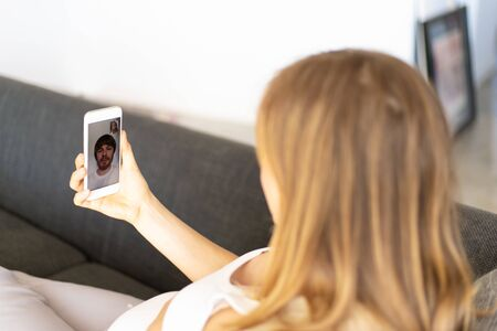 Expectant mother using cellphone for internet call. Pregnant woman lying on couch, holding mobile phone, talking to husband. Video call concept Stock Photo
