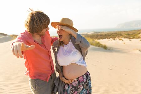 Playful husband and pregnant wife having fun on beach. Smiling young husband pointing to camera. Careless woman holding hand near forehead. Pregnancy concept 版權商用圖片