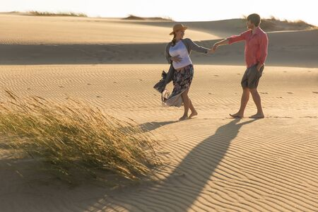 Happy spouse holding hands together during stroll. Smiling young woman and man having fun on seashore. Pregnancy concept