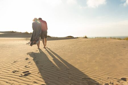 Back view of young couple strolling on sandy beach. Husband and wife strolling on seashore during vacation. Vacation concept