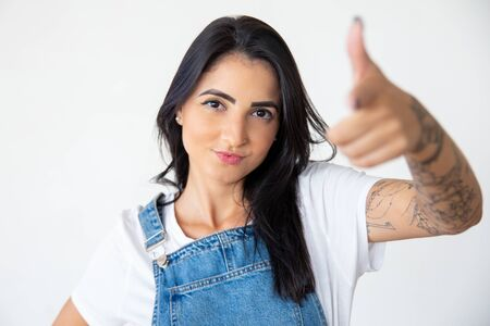 Joyful young woman pointing to camera. Confident smiling lady posing on white background. Concept of indication