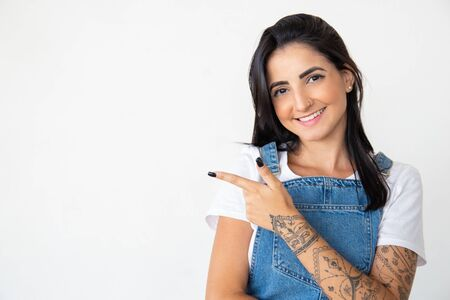 Smiling young woman pointing to left. Positive lady showing empty copyspace on white background. Concept of indication Reklamní fotografie