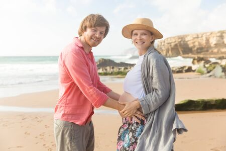 Smiling husband and pregnant wife standing on beach. Happy future father holding hands on belly. Pregnancy concept