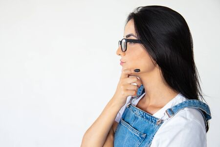 Side view of thoughtful young woman in eyeglasses. Serious brunette holding hand on chin. Thinking concept