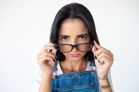 Closeup shot of beautiful serious young woman in eyeglasses. Closeup shot of beautiful young woman in eyeglasses looking at camera. Female beauty concept