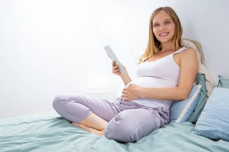 Happy expectant mom with tablet relaxing in bedroom. Pregnant woman sitting on bed, holding digital device, touching belly, looking at camera. Digital technology concept