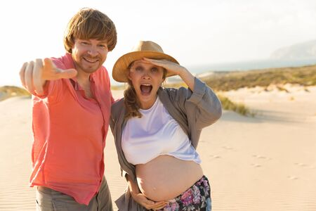 Happy husband and pregnant wife having fun on beach. Smiling young husband pointing to camera. Careless woman looking at camera. Pregnancy concept